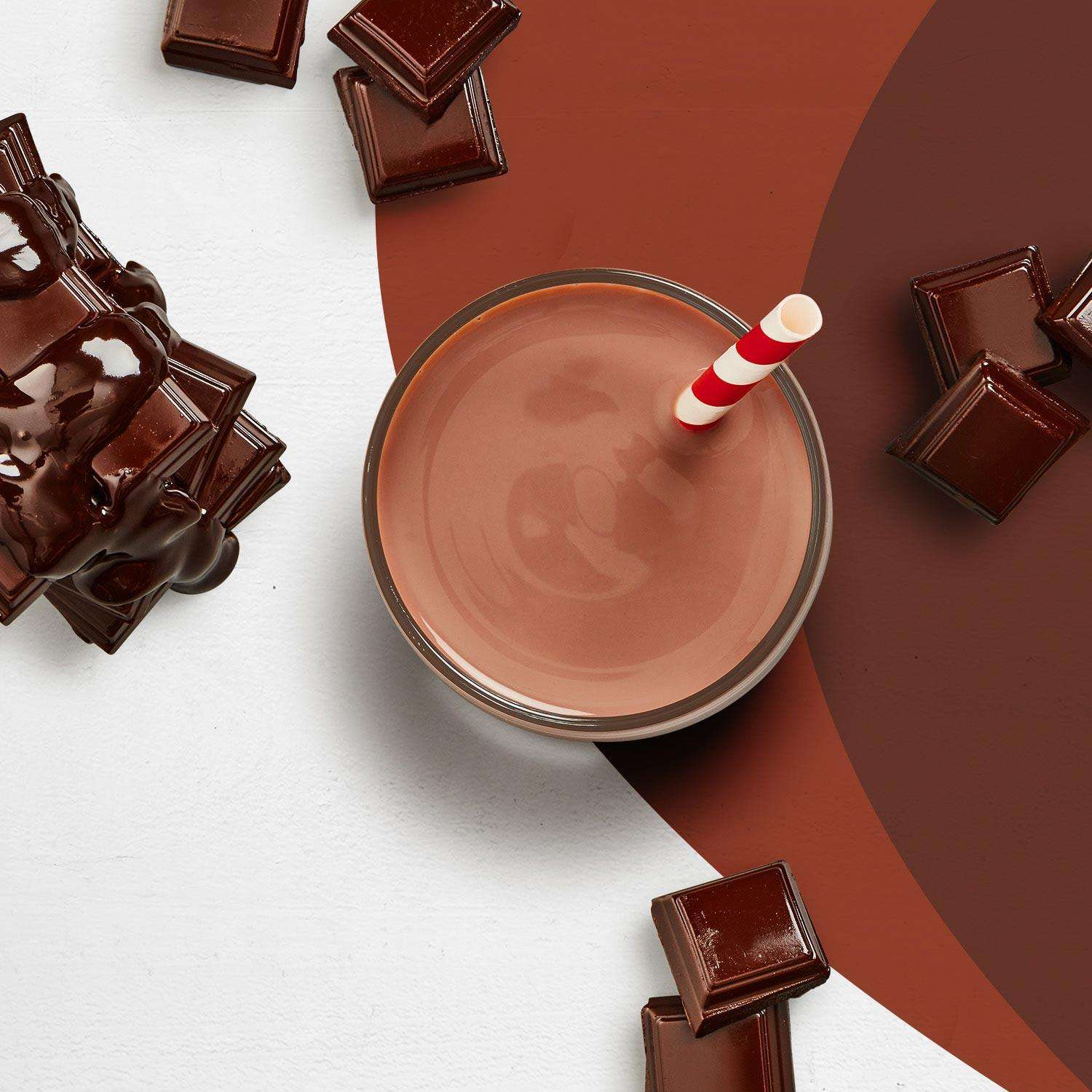 A chocolate Premier Protein shake surrounded by pieces of chocolate.