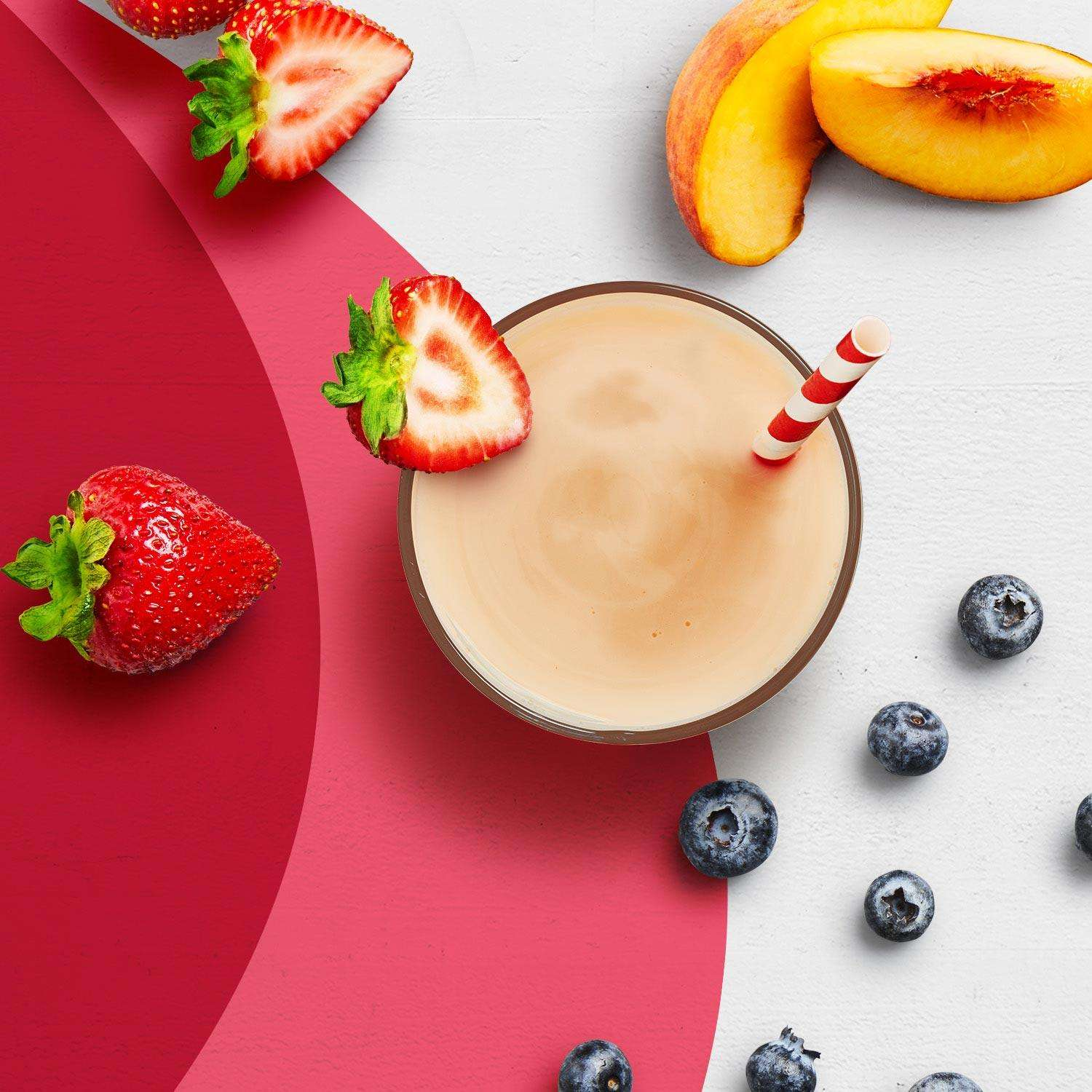 A strawberries and cream Premier Protein shake next to strawberries, peaches and blueberries.