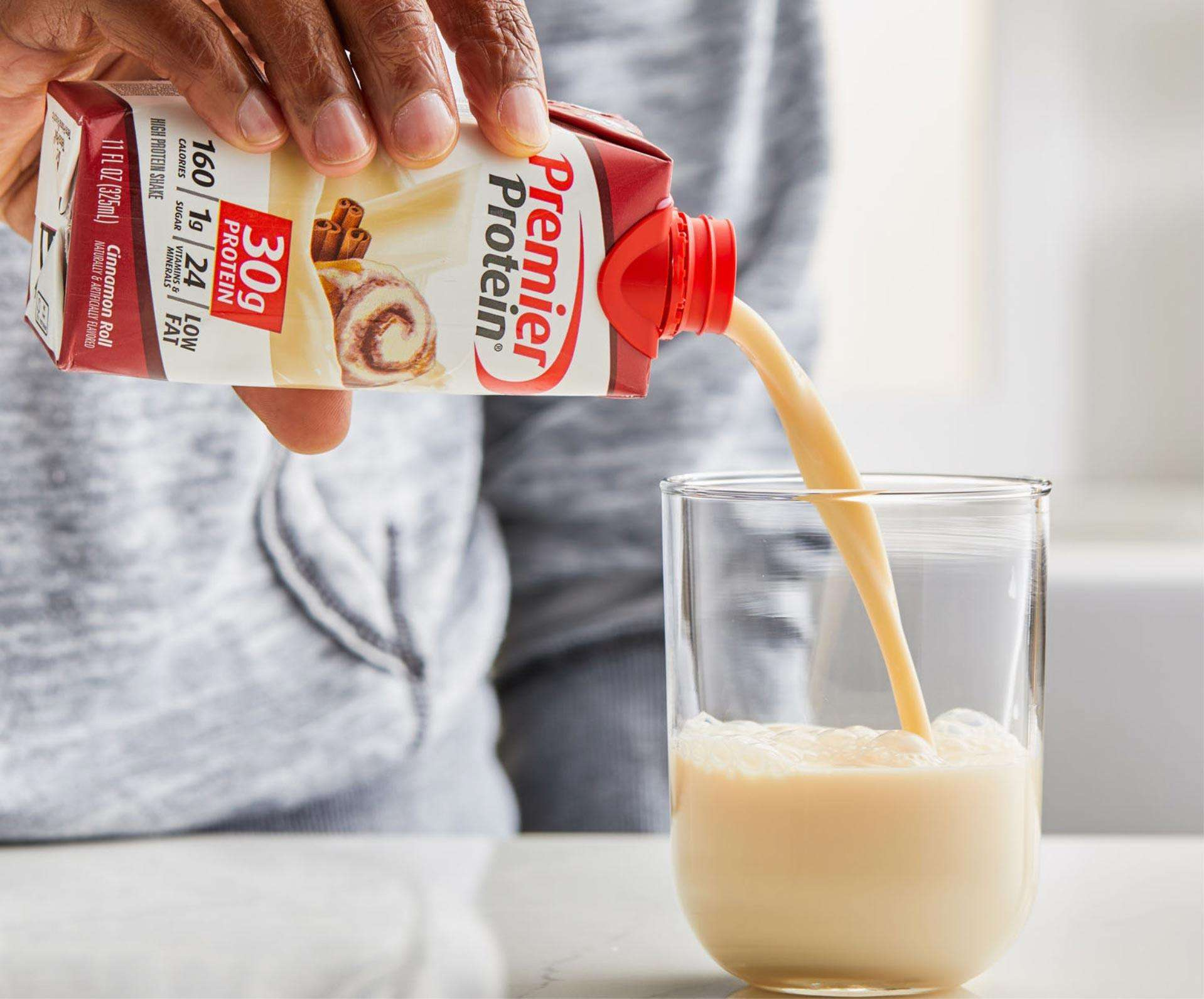 Cinnamon Roll Premier Protein Shake being poured into a cup.