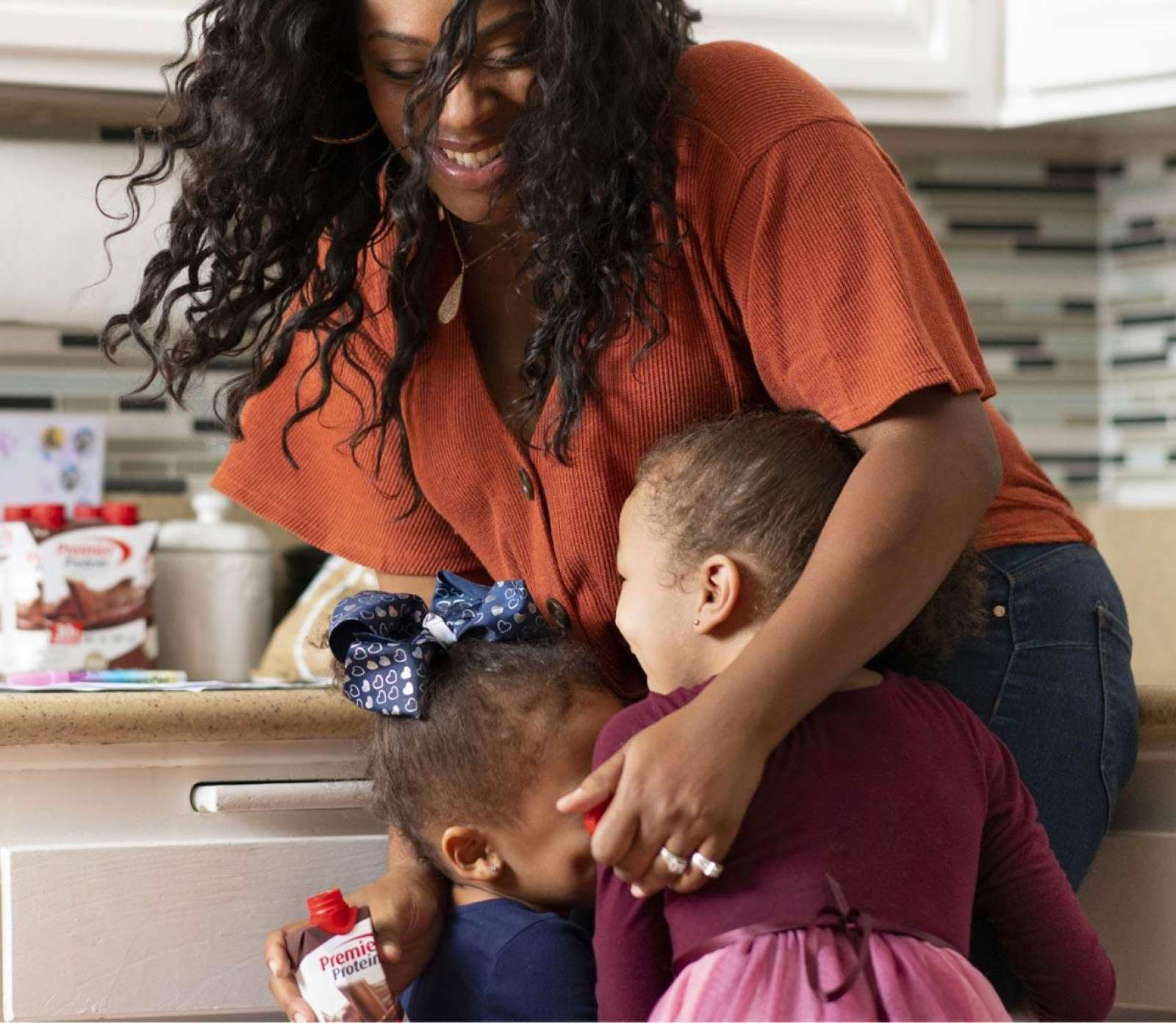 A women hugging her active kids while in her kitchen.