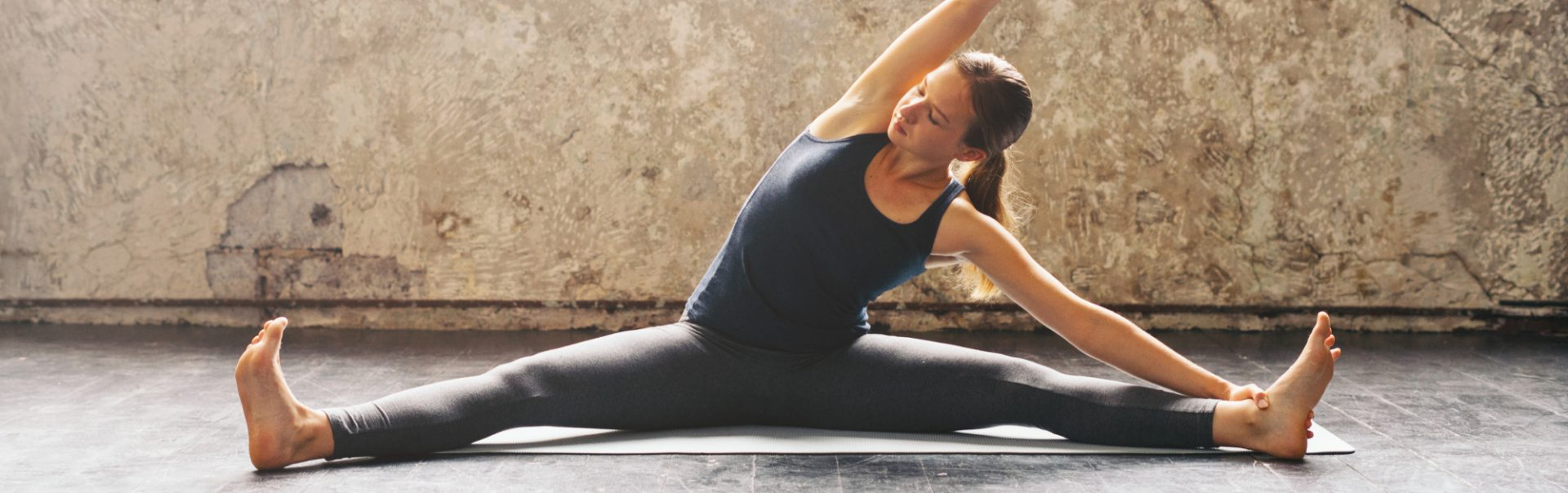 A woman seated on a yoga mat stretching to the side