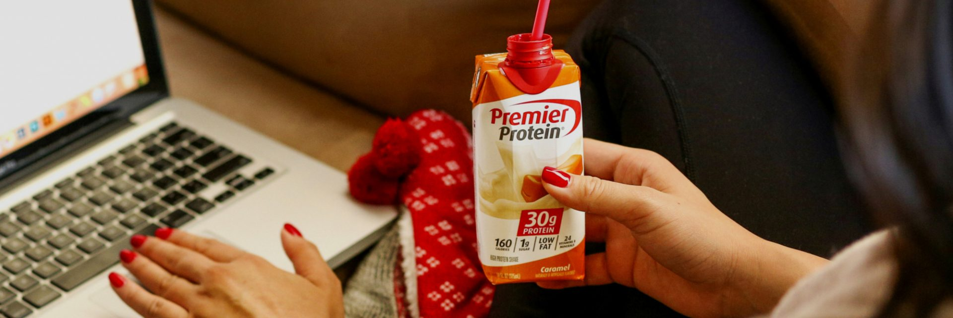 A women at a computer drink a Premier Protein Caramel Protein Shake