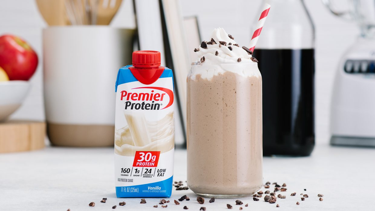 Protein Coffee Shake in a large glass with a red and white striped straw next to a Vanilla Premier Protein Shake in a tetra package.