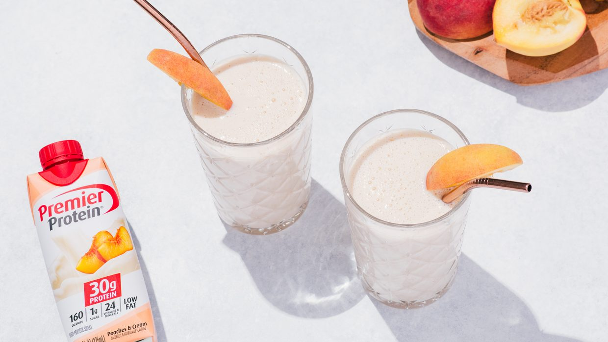 Two Peach smoothies in glasses with metal straws and peach slice garnish. A Peaches & Cream Premier Protein shake in a tetra package is lying on the table, along with a sliced peach.