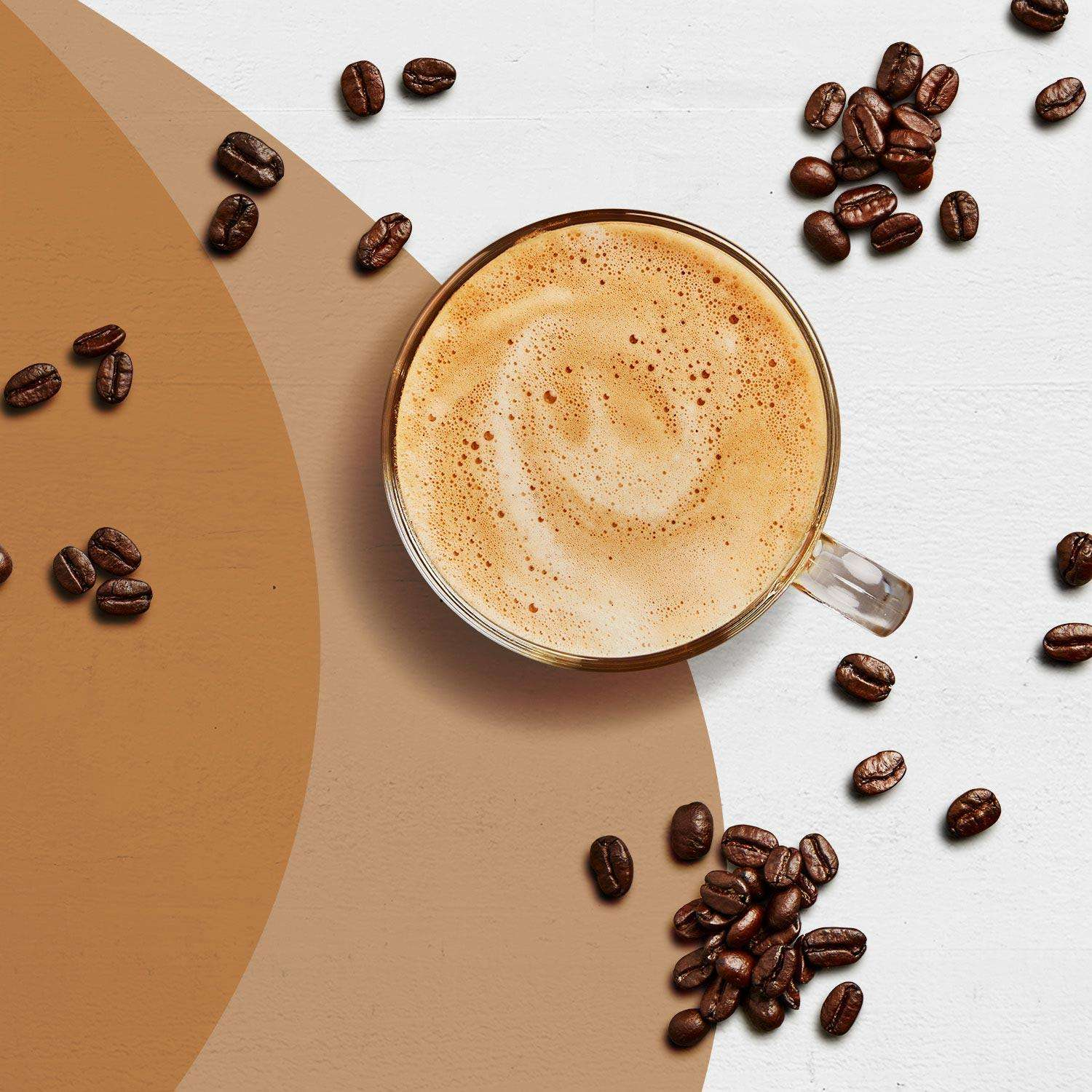 A Cafe Latte Premier Protein shake surrounded by coffee beans..