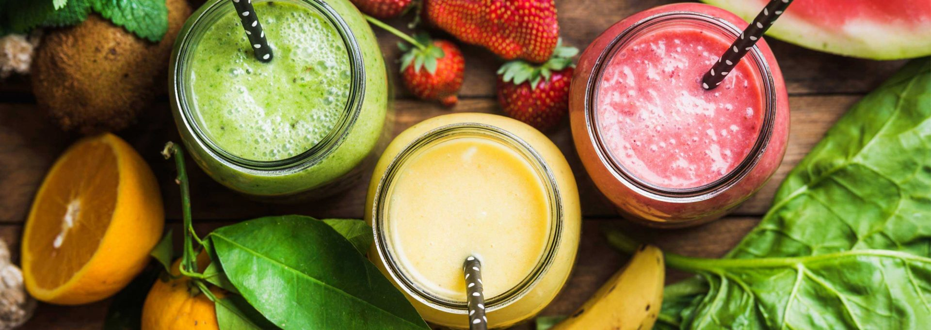 Three multicolored smoothies in jars with straws.