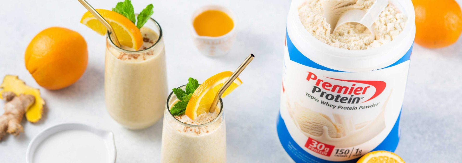 Two Premier Protein shakes in cups made with Premier Protein Vanilla Shake Powder.