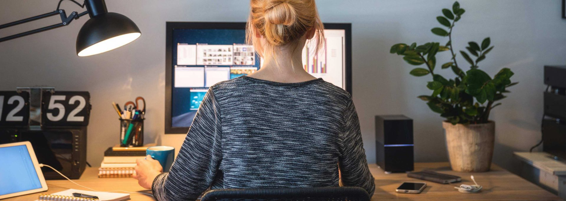 A woman sitting at her desk, working on a computer.