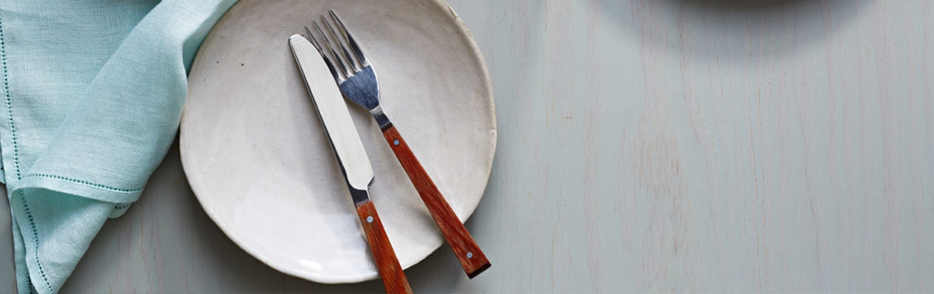 An empty plate with a fork and knife.