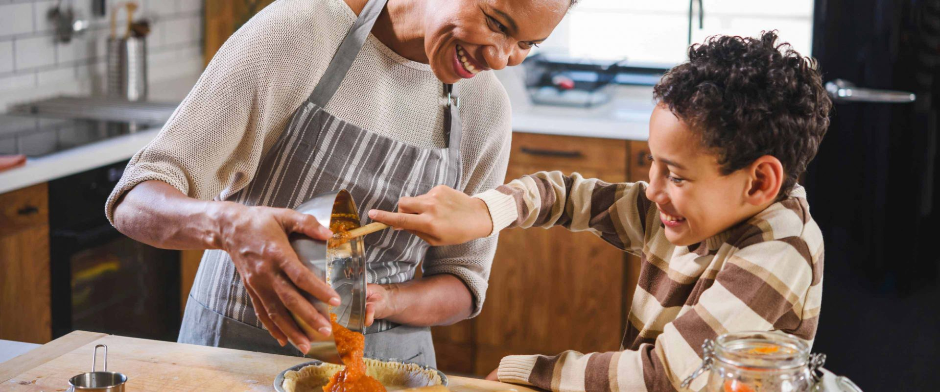 A mother and her young son in their kitchen, baking.