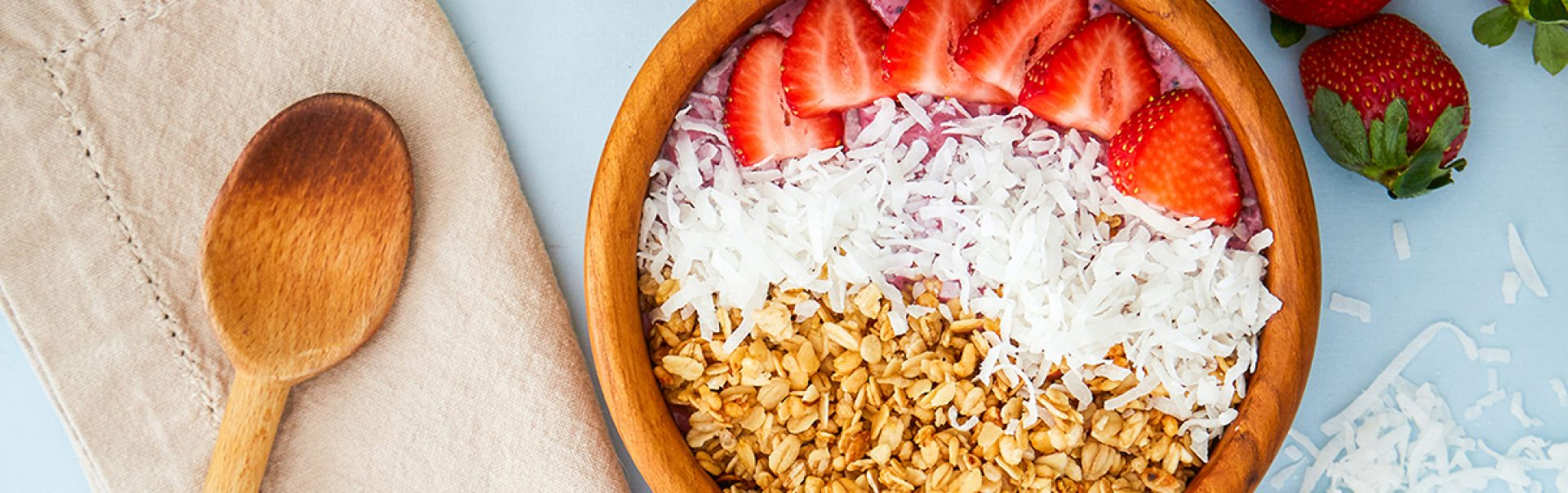 A bowl of strawberries, coconut and grains.