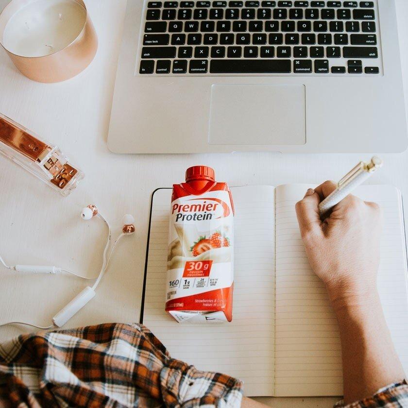 Une boisson protéinée Premier sur table à côté d'un ordinateur portable ouvert.