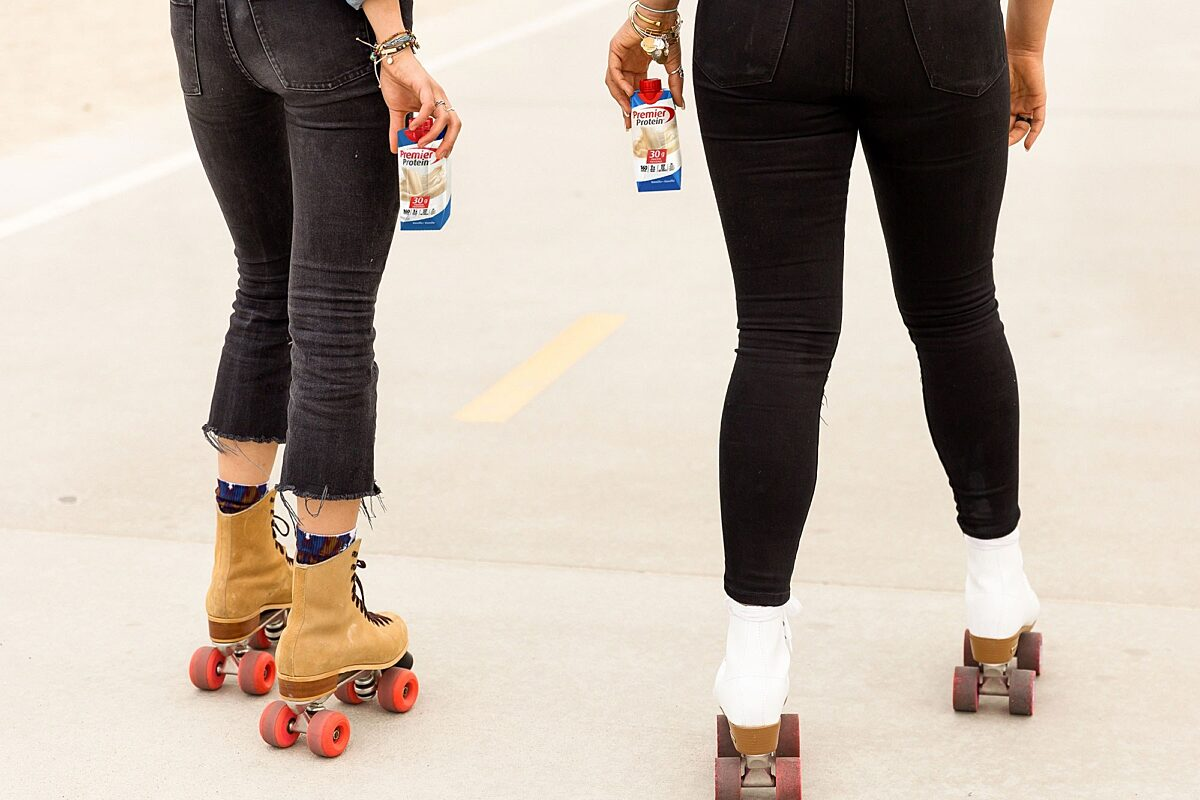 Two people roller skating with Vanilla Premier Protein shakes.