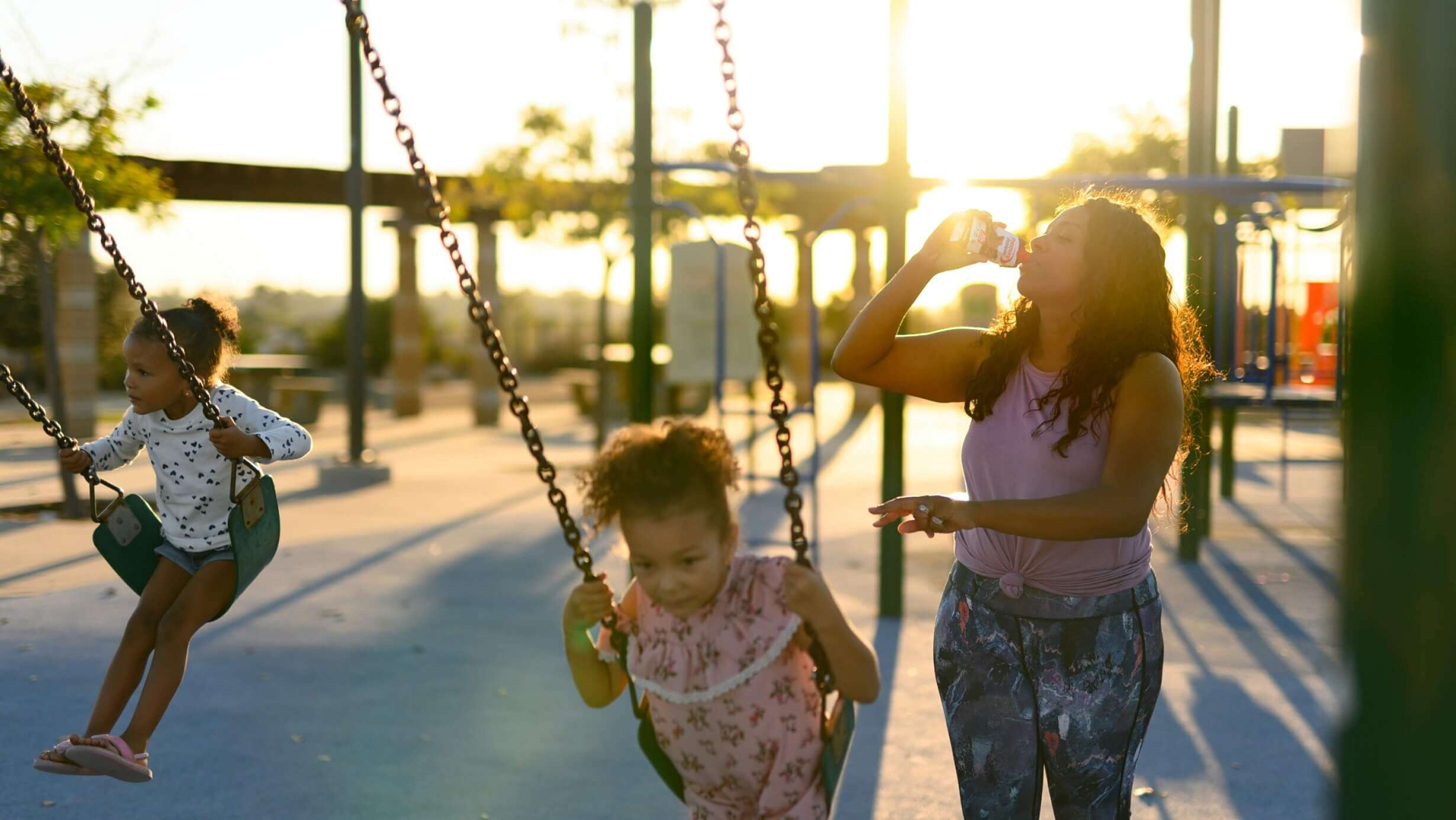 Charmaine enjoying a Chocolate Premier Protein Shake at a playground with her children.