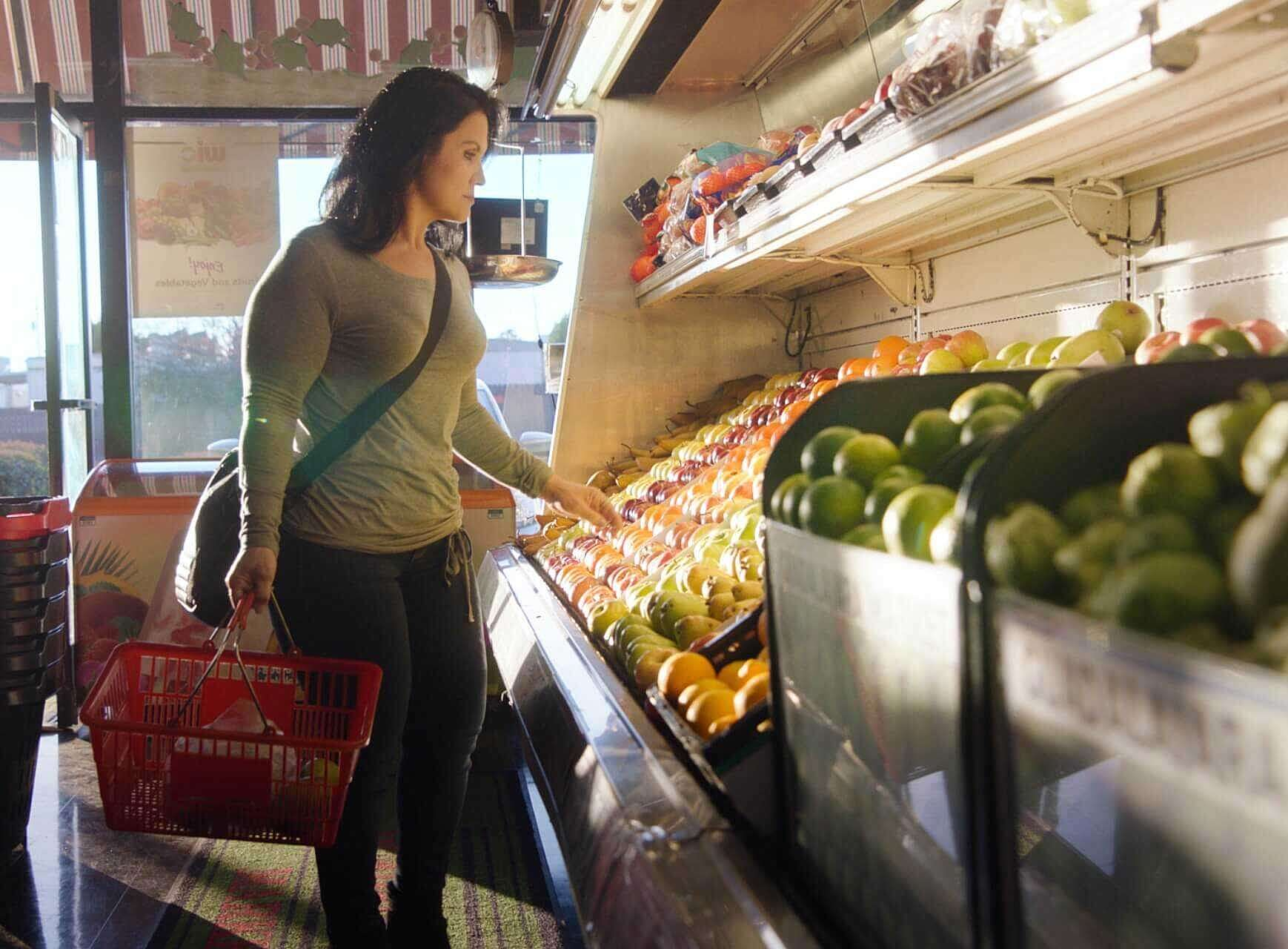 Araceli in the produce section of a grocery store.