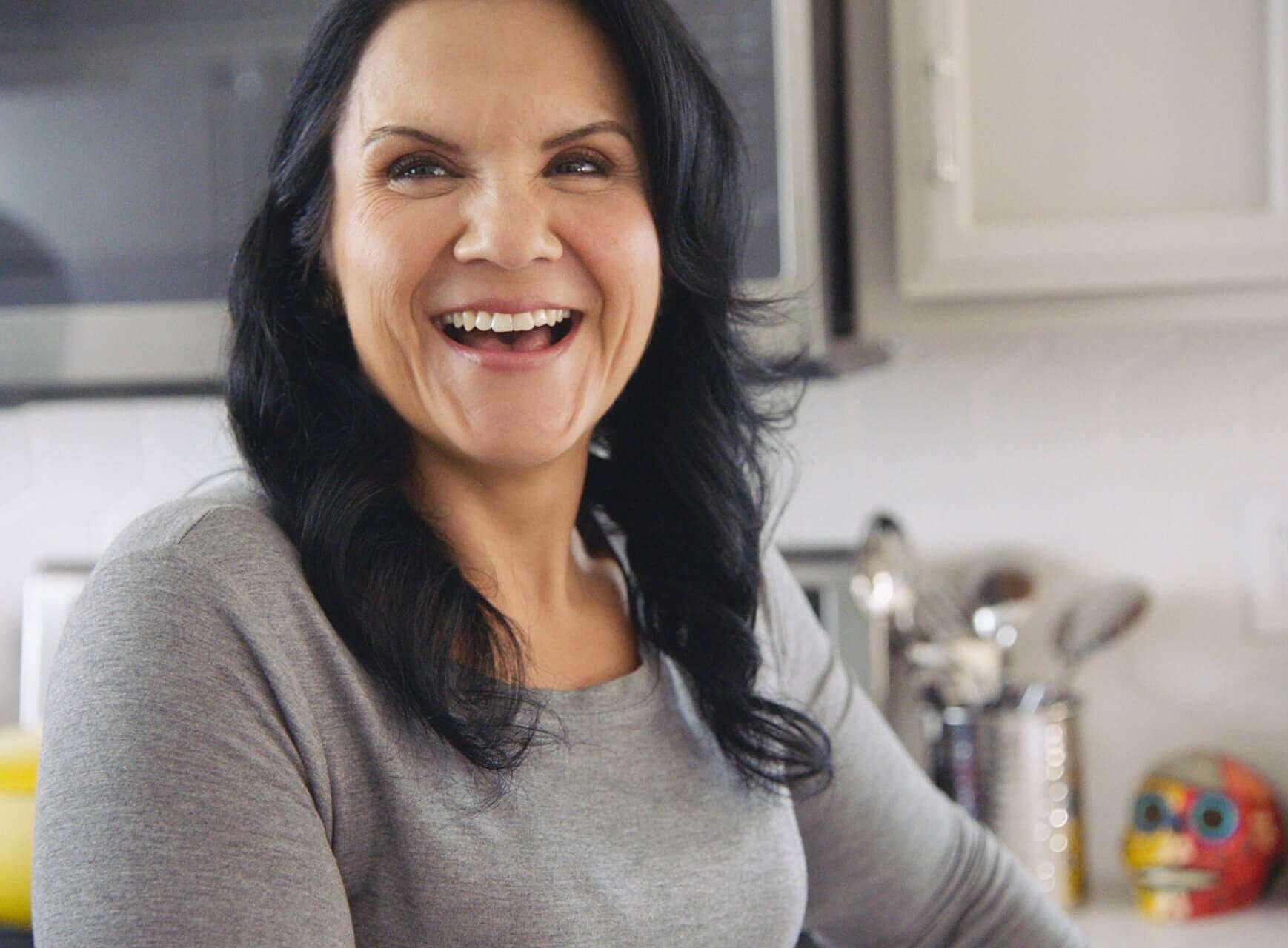 Araceli smiling in her kitchen.