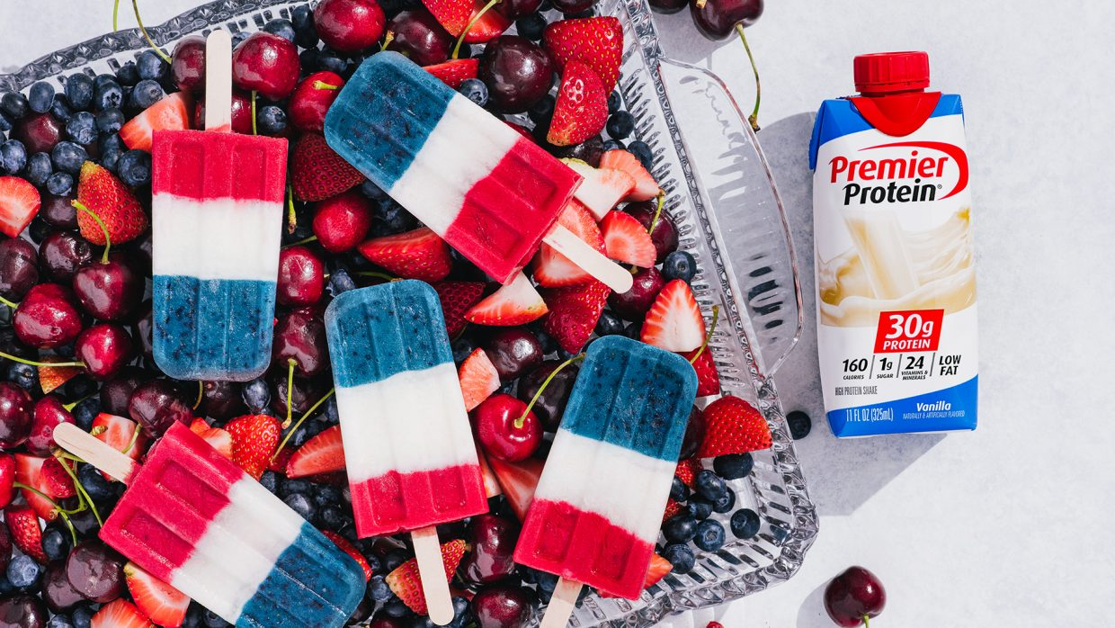 Four 4th of July Protein Smoothie Pops arranged on top of a container of cherries, strawberries, and blueberries. A Vanilla Premier Protein Shake in a tetra package is laying on the table nearby.